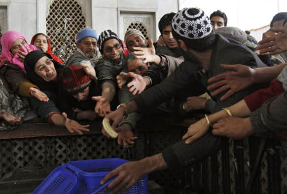 A Kashmiri man distributes bread to other devotees outside the shrine of Sufi saint Hazrat Sheikh Hamza Makhdoom, commonly known as Sultan-Ul-Arifeen, as she offers prayers during the saint`s Urs, or yearly commemoration, in Srinagar.