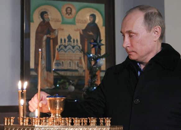 Russian President Vladimir Putin lights a candle as he attends the Christmas service in the Trinity St. George Monastery in Sochi, Russia.