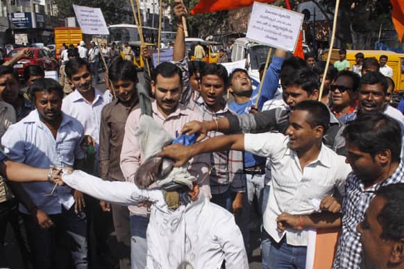 Activists of the right-wing Hindu nationalist Vishwa Hindu Parishad (VHP) shout slogans and beat an effigy of Majlis-e-Ittehadul Muslimeen (MIM) leader Akbaruddin Owaisi during a protest against his alleged hate speech in Hyderabad.