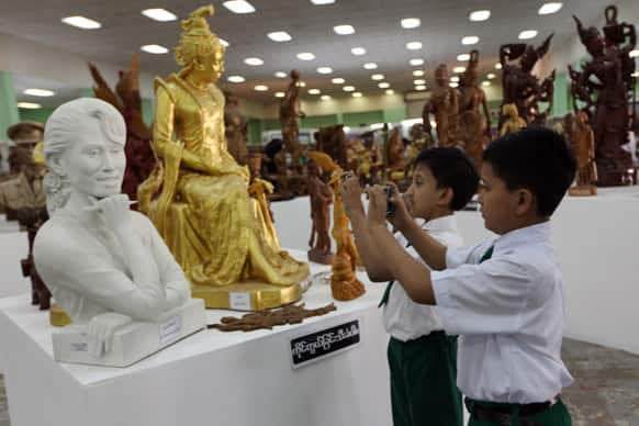 Two boys take photographs of a statue of Myanmar opposition leader Aung San Suu Kyi displayed at the