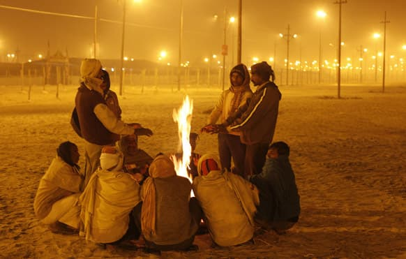 Indians warm themselves around a bonfire at the Sangam, the confluence of rivers Ganges, Yamuna and the mythical Saraswati in Allahabad.
