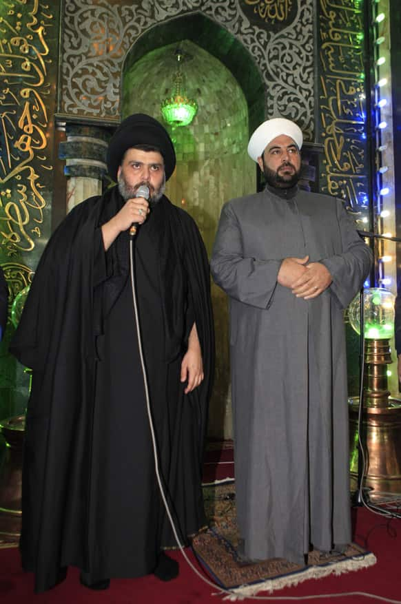 Firebrand Shiite cleric Muqtada al-Sadr, left, address worshippers as a Sunni cleric Anas al-Issawi, right, listen during the Friday prayers at Abdul-Qadir al-Gailani Sunni mosque in Baghdad, Iraq.