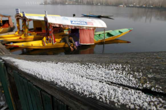 A Kashmiri boatman breaks the frozen surface of the Dal lake as frost is seen at the banks in Srinagar.