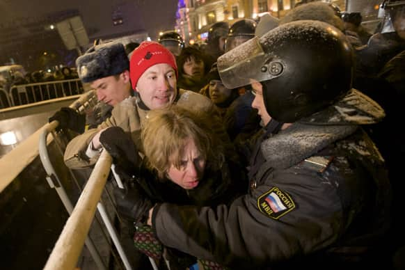Russian police officers push protesters off Triumphalnaya square during an unsanctioned rally in downtown Moscow, Russia.