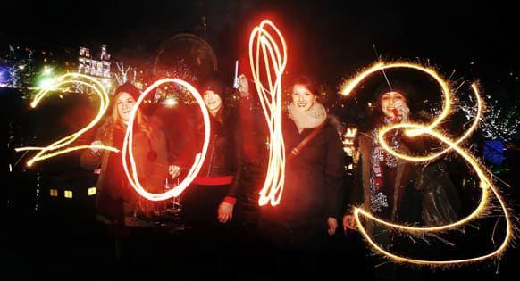 Katy Saunders, left, Alex Mueller, center left, Rebekka Frank and Arina Motamedi, right, play with sparklers ahead of welcoming in the new year during the 2013 Edinburgh Hogmanay celebrations, Scotland.