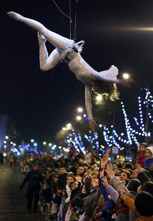 An artist performs over the crowd during the 'Cabalgata de Reyes,' or the Three Wise Men parade in Madrid.