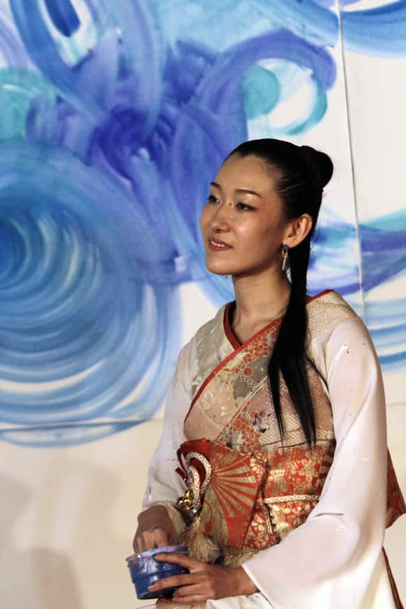 Japanese painter Saori Kanda pauses, as she paints a 'music-inspired painting' on a canvas during the Art & Cultural Folk Festival in Kolkata.