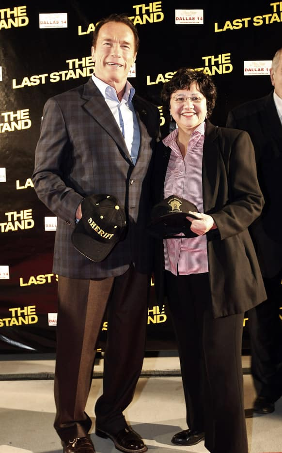 Arnold Schwarzenegger and Dallas County Sheriff Lupe Valdez pose with Sheriff caps during the red carpet premiere of