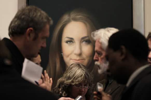 Members of the media talk to artist Paul Emsley, center right, in front of his newly-commissioned portrait of Kate, Duchess of Cambridge, on display at the National Portrait Gallery in London.