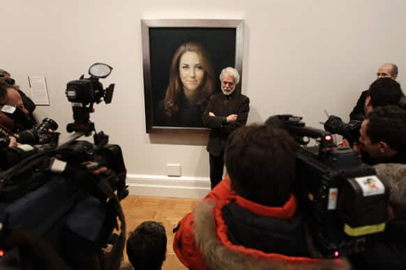 Artist Paul Emsley poses for photographers next to his newly-commissioned portrait of Kate, Duchess of Cambridge, on display at the National Portrait Gallery in London.