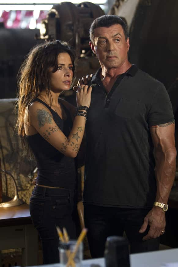 This film image released by Warner Bros. Pictures shows Sarah Shahi, left, and Sylvester Stallone in a scene from