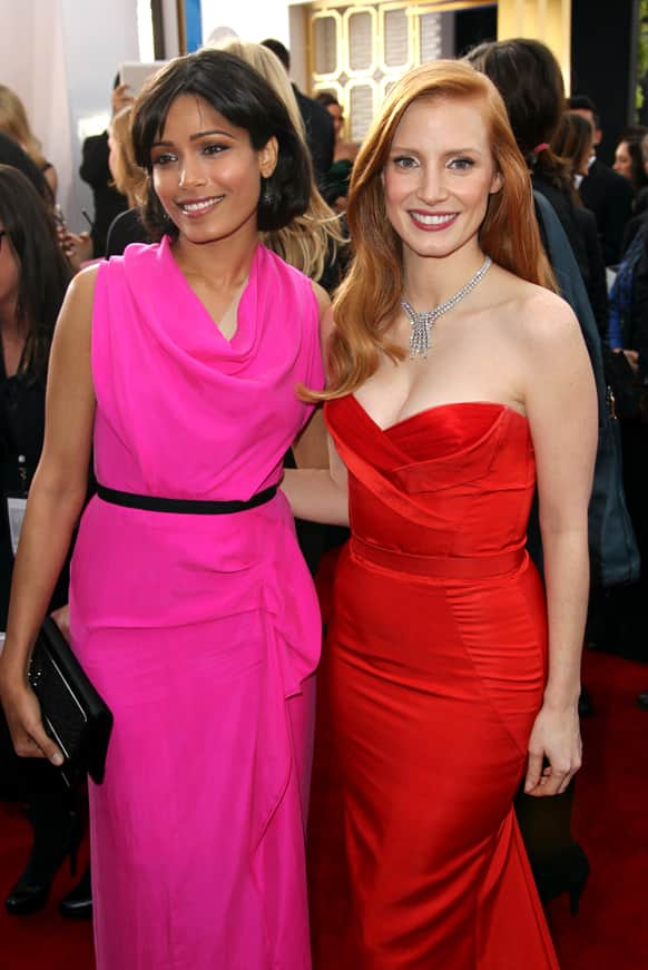 Actresses Freida Pinto, left, and Jessica Chastain arrive at the 19th Annual Screen Actors Guild Awards at the Shrine Auditorium in Los Angeles.