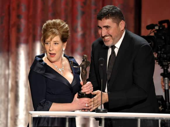 "Phyllis Logan, left, accepts the award from Alfred Molina for outstanding ensemble in a drama series for ""Downton Abbey"" at the 19th Annual Screen Actors Guild Awards at the Shrine Auditorium."