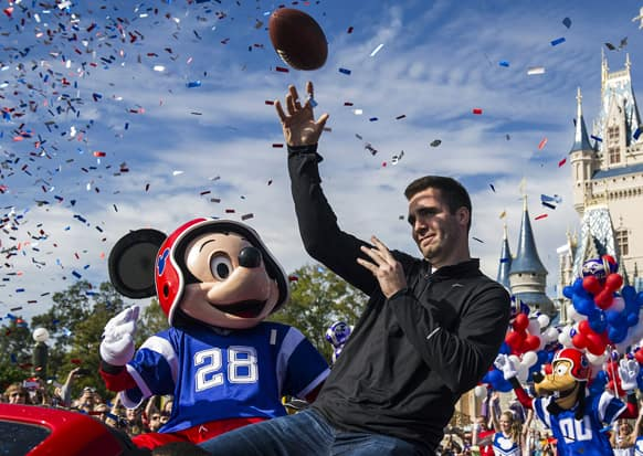 Super Bowl MVP Joe Flacco rides with the character Mickey Mouse in a parade through the Magic Kingdom at Walt Disney World Resort in Lake Buena Vista, Fla.