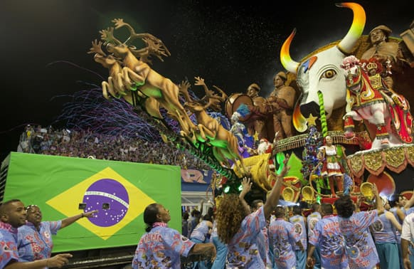 Dancers from the Rosas de Ouro samba school surround their float during a carnival parade in Sao Paulo, Brazil.