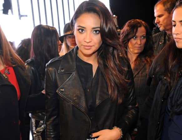 Actress Shay Mitchell arrives on the runway before the showing of the DKNY Fall 2013 collection during Fashion Week, in New York.