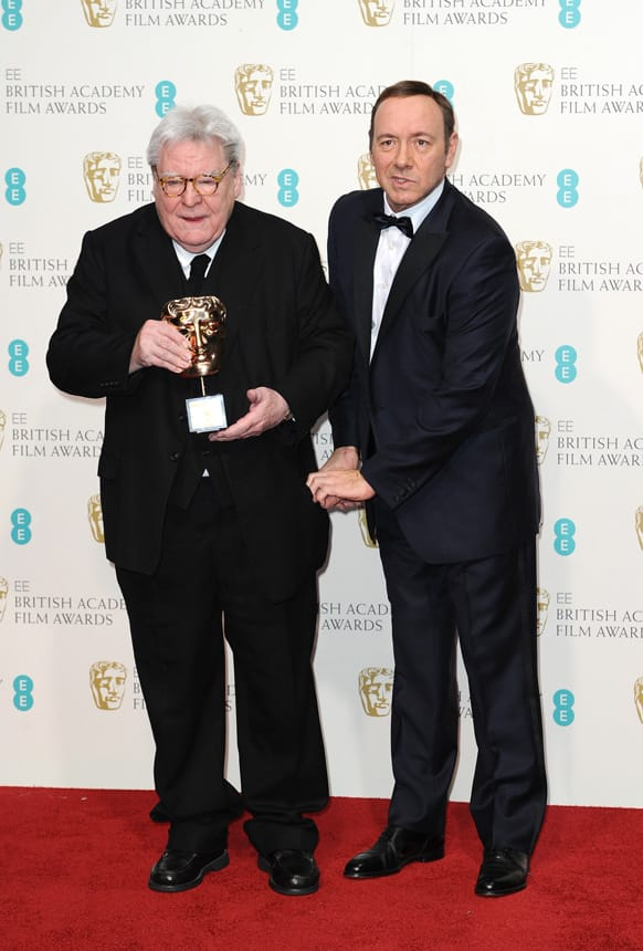 British director Alan Parker, left, with the Fellowship award, and American producer-actor Kevin Spacey pose backstage at the BAFTA Film Awards at the Royal Opera House.