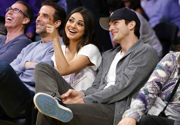 Actress Mila Kunis, left, and Ashton Kutcher, right sit courtside together at the NBA basketball game between the Phoenix Suns and Los Angeles Lakers in Los Angeles.