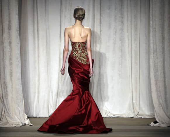 A model returns backstage after walking a runway at the conclusion of the Marchesa Fall 2013 fashion show at Fashion Week in New York.