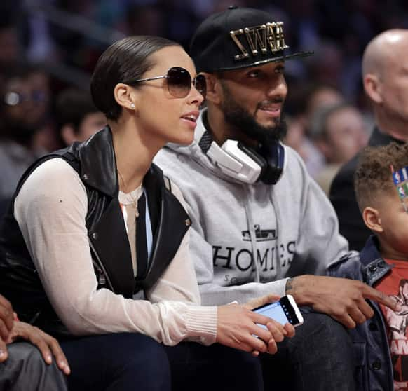 Singer Alicia Keys, left, and her husband Swizz Beatz sit courtside during NBA All-Star Saturday Night basketball in Houston.