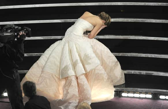 Actress Jennifer Lawrence stumbles as she walks on stage to accept the award for best actress in a leading role for