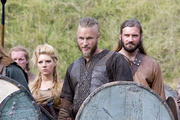 This image released by History shows Katheryn Winnick, as Lagertha, left, Travis Fimmel, as Ragnar, center, and Clive Standen as Rollo in a scene from