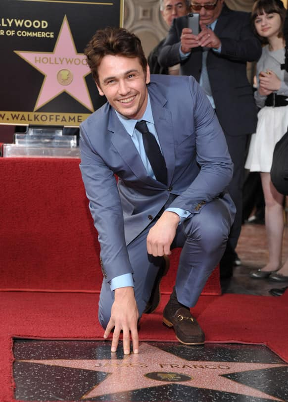 Actor James Franco poses with his star at a ceremony honoring him on the Hollywood Walk of Fame on, in Los Angeles.