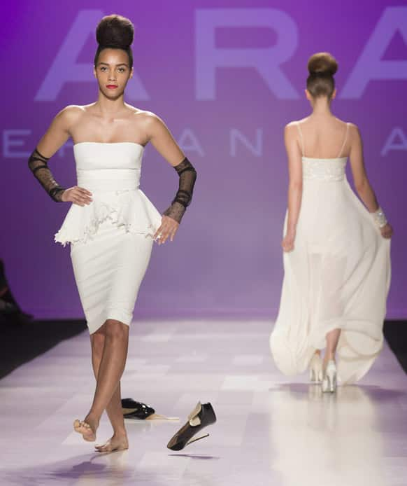 A model kicks off her remaining shoe after the other one slipped off her foot as she shows a creation from Stephan Caras while walking the runway during Toronto Fashion Week in Toronto.
