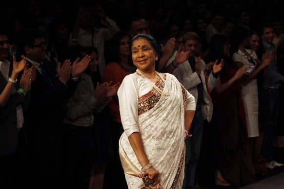 Veteran Bollywood singer Asha Bhosale showcases a creation of Manish Malhotra during the first day of Lakme fashion week, Mumbai.