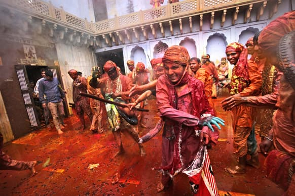 Villagers from Nandgaon throw color dye on the villagers from Barsana as they arrive at the Nandagram temple famous for Lord Krishna and his brother Balram, during Lathmar holy festival, in Nandgaon.
