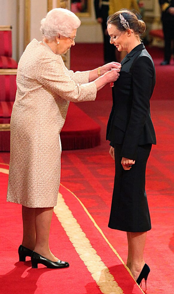 Fashion designer Stella McCartney, right, receives her Officer of the British Empire (OBE) medal from Britain's Queen Elizabeth II during an Investiture ceremony at Buckingham Palace in central London.