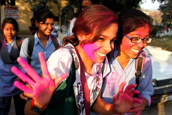 An Allahabad University student, face smeared with colored powder, gestures as she celebrates Holi, the festival of colors, in Allahabad.