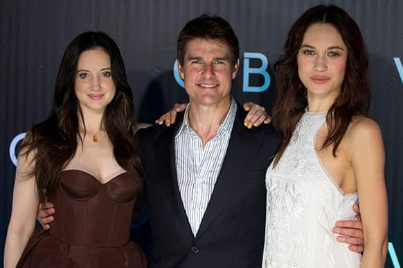 Actor Tom Cruise, center, poses for pictures with actresses Andrea Riseborough, left, and Olga Kurylenko during the premiere of their new sci-fi action movie