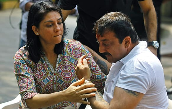 Bollywood actor Sanjay Dutt, right, breaks down as his sister Priya Dutt tries to console him during a press conference at his residence in Mumbai.