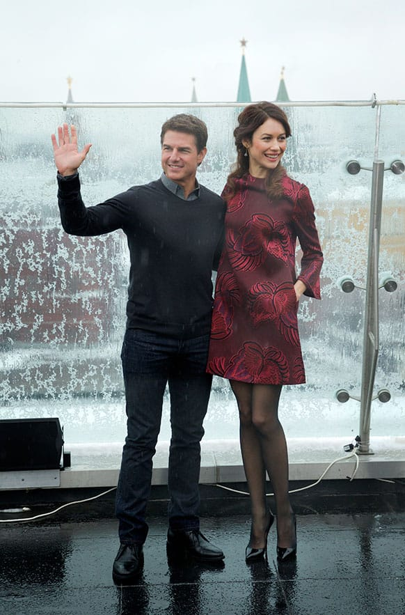 Hollywood actor Tom Cruise, left, and actress Olga Kurylenko pose during a photo call to promote their new movie Oblivion on the roof of a hotel in Moscow, with the Kremlin in the background.