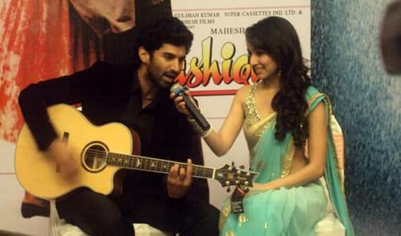 Shraddha Kapoor holds the mike as Aditya Roy Kapoor sings at the 'Aashiqui 2' music launch.