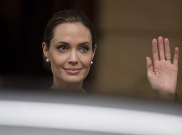 Angelina Jolie waves to the media as she leaves a G8 Foreign Ministers meeting on sexual violence against women in London.
