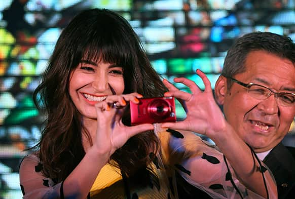 Bollywood actor Anushka Sharma takes a photograph as President and CEO Canon India Kazutada Kobayashi watches during the launch of a new range of Canon cameras, including W-Fi enabled ones, in New Delhi.