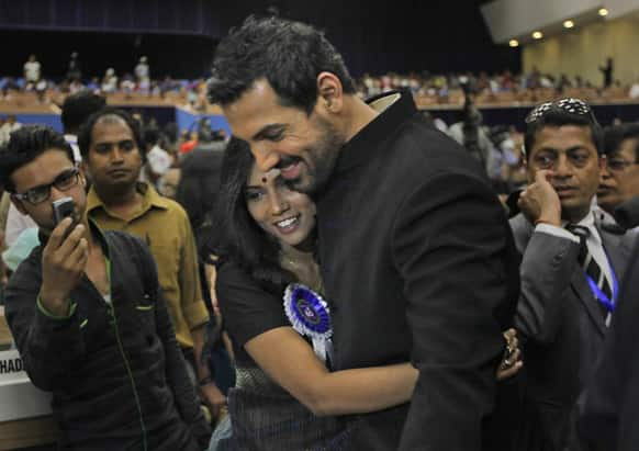 Bollywood actor John Abraham hugs fellow actor Usha Jadhav during the National Film Awards 2012, in New Delhi. Abraham's debut production