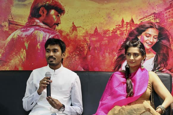 """Dhanush, answers a question as actress Sonam Kapoor watches during a press conference to promote their new movie """"Raanjhnaa"""" in Ahmadabad. The film will be released in India on June 21."""