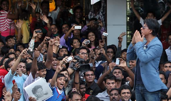 Shah Rukh Khan stand on his car and greets fans during a promotional event for his film