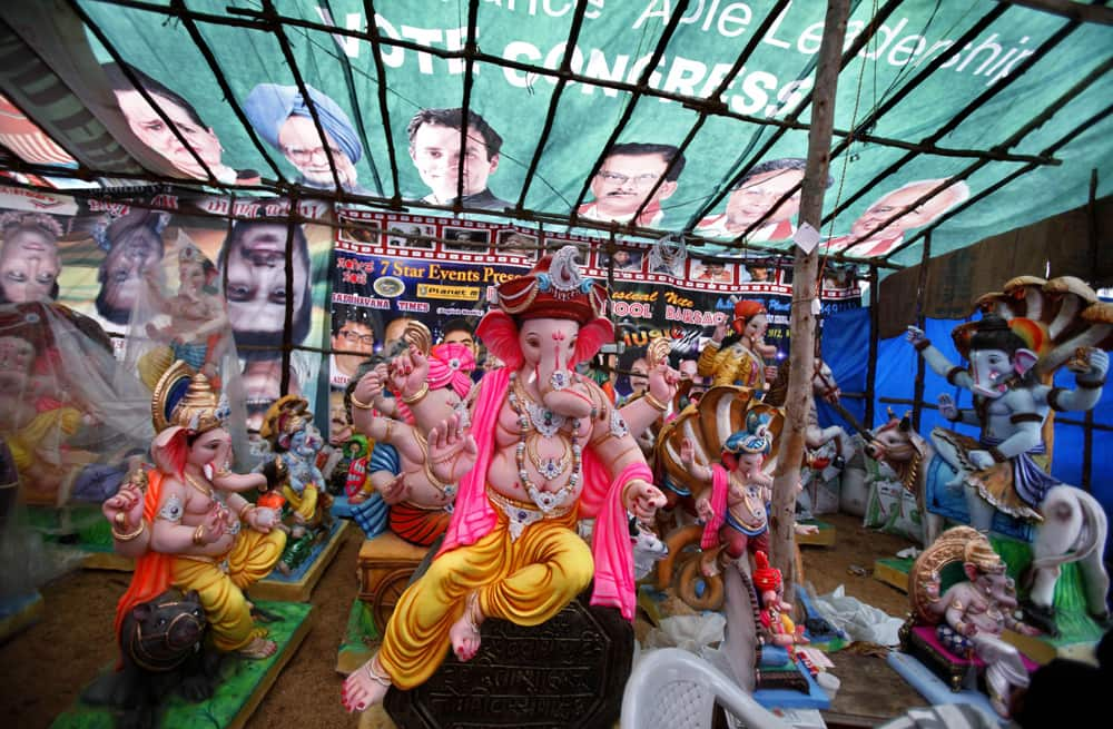 Idols of the Hindu god Ganesh are covered with a banner featuring Congress party leaders ahead of Ganesh Chaturthi festival at a workshop in Bangalore.