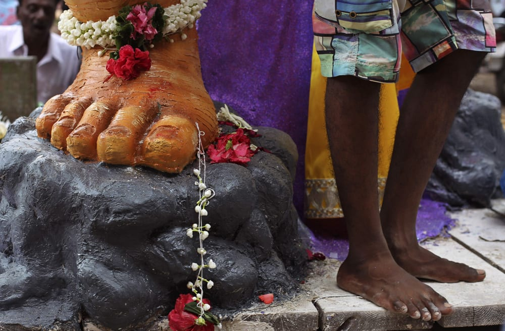 A devotee stands near a huge idol of the Hindu god Ganesh as it is transported to a place of worship in Mumbai.