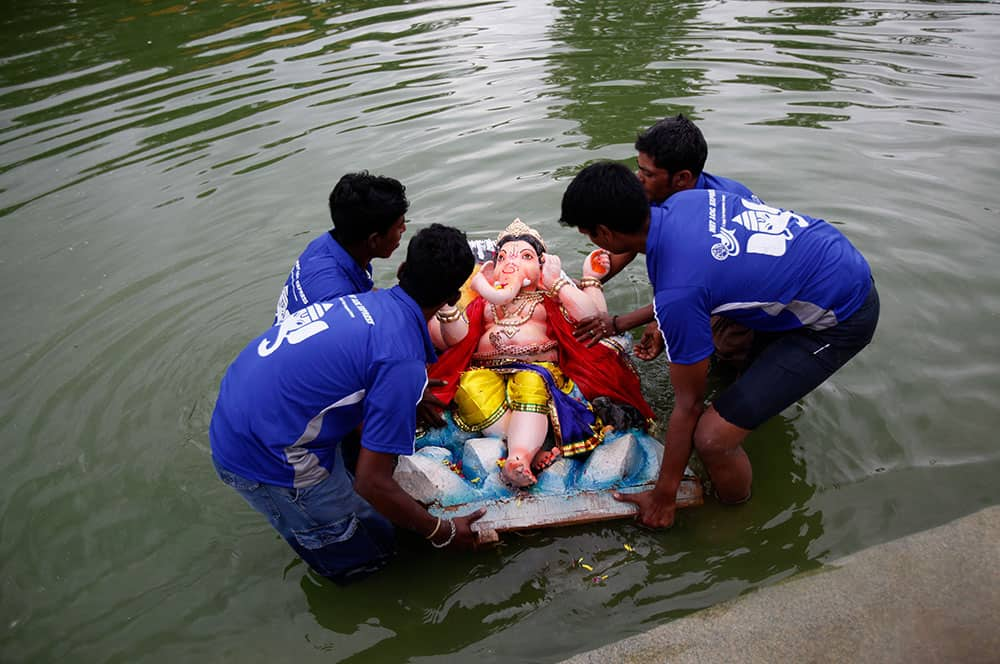 Volunteers prepare to immerse an idol of elephant-headed Hindu god Ganesha in a pond during Ganesh Chaturthi festival celebrations in Bangalore.