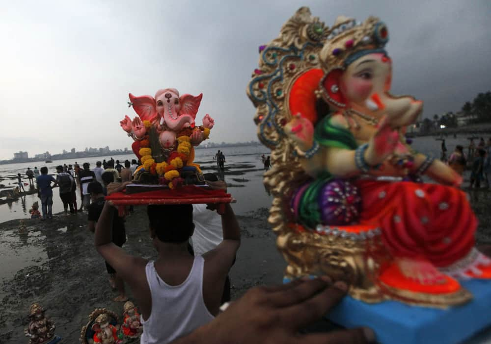 Devotees prepare to immerse idols of elephant-headed Hindu god Ganesha in the Arabian Sea during Ganesh Chaturthi festival celebrations in Mumbai.