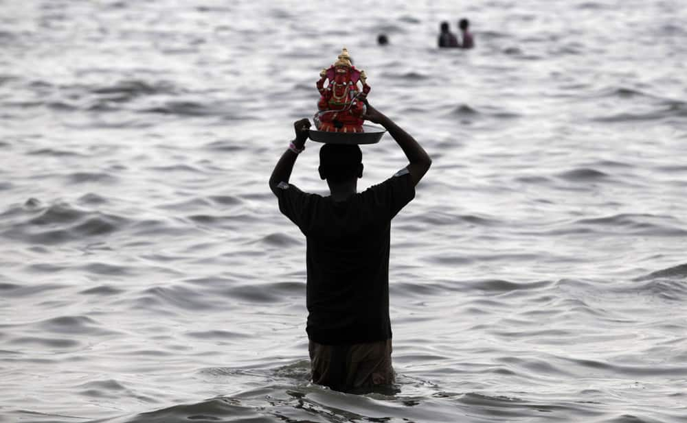 A devotee prepares to immerse an idol of elephant-headed Hindu god Ganesha in the Arabian Sea during Ganesh Chaturthi festival celebrations in Mumbai.