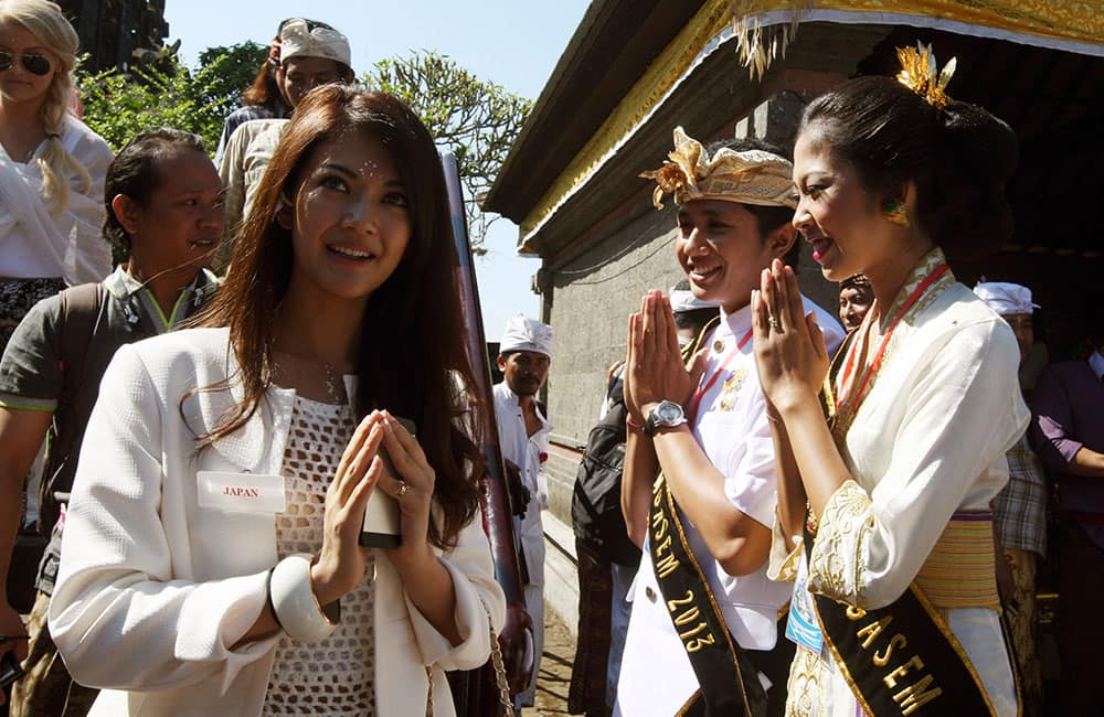 Balinese couple, right, welcomes Miss Japan Michiko Tanaka, left, and other Miss World pageant contestants during their visit to a Hindu temple in Besakih, Bali, Indonesia. The Miss World contest opened on the resort island of Bali Sunday, with the final to be held on Sept. 28.