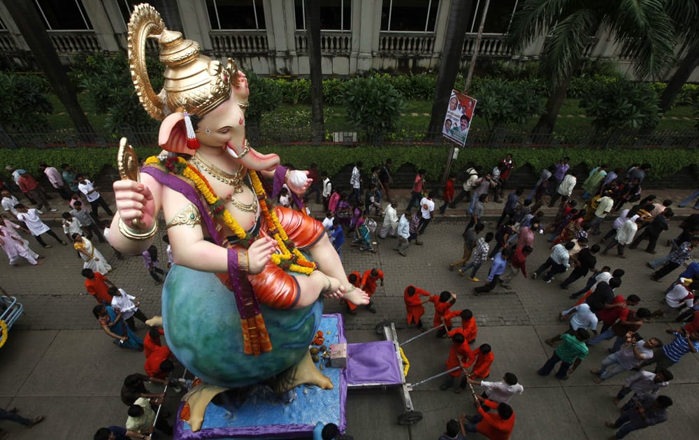 Devotees take an idol of elephant headed Hindu god Ganesha through a street for immersion in the Arabian Sea in Mumbai.