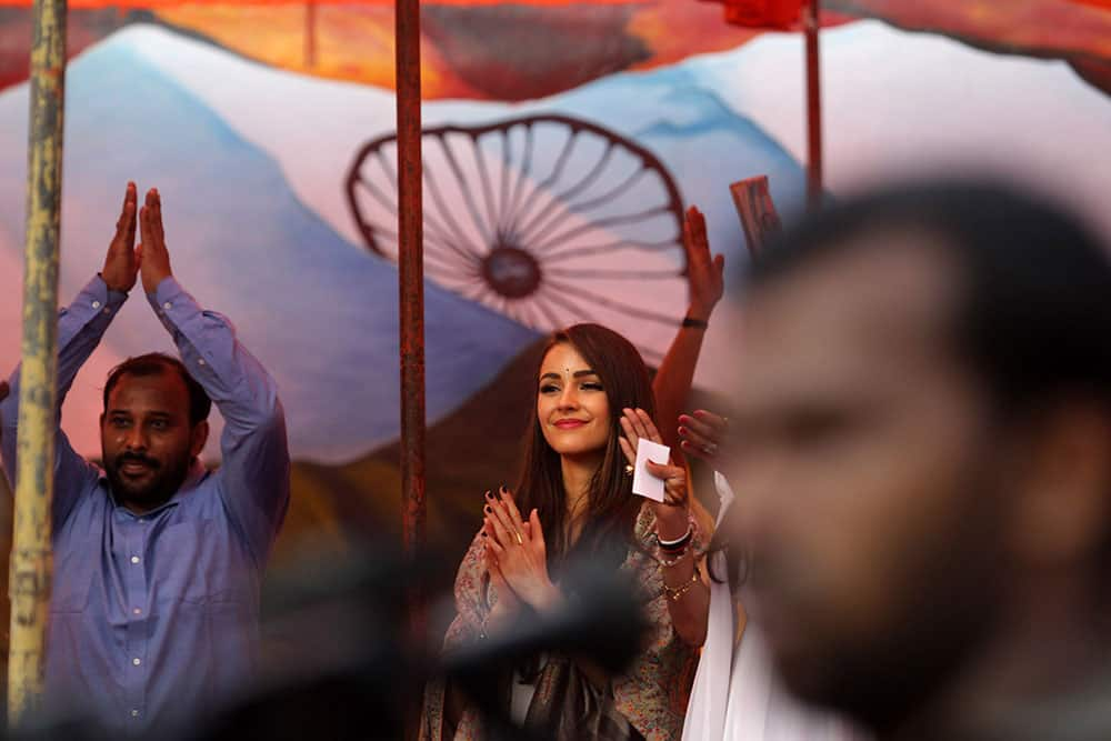 Miss Universe Olivia Culpo, center, applauds inmates as she stands before a painting of the Indian flag during a visit to the Tihar Jail in New Delhi.