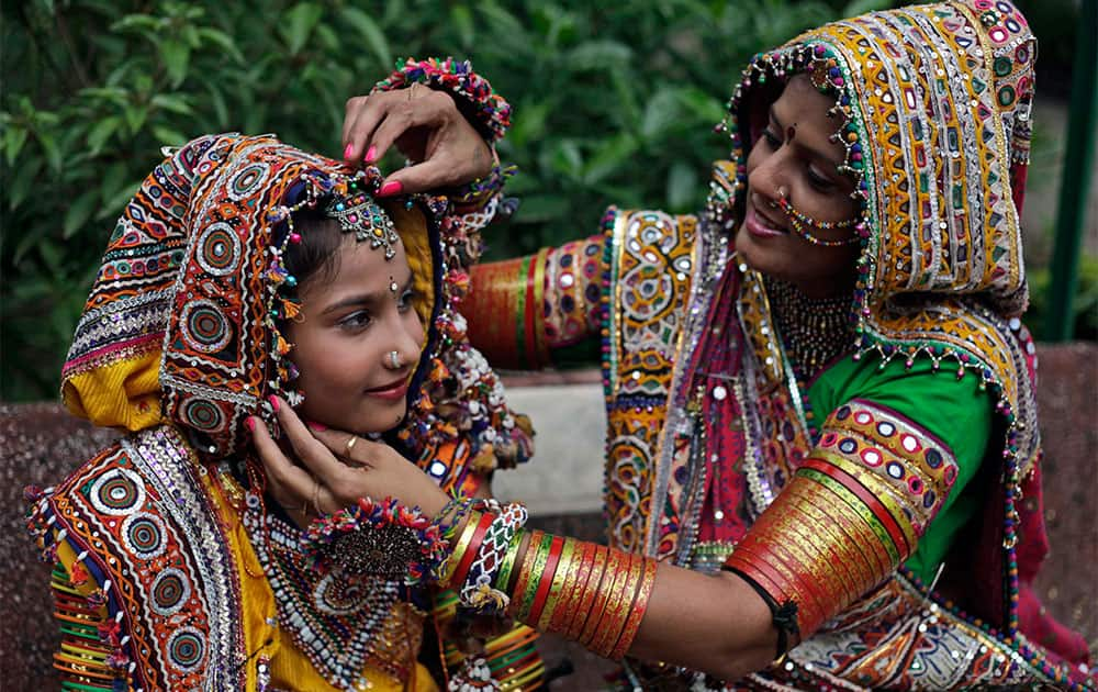 A woman, dressed in traditional finery, helps a girl with her costume before practicing the Garba dance ahead of the Navratri festival in Ahmadabad.